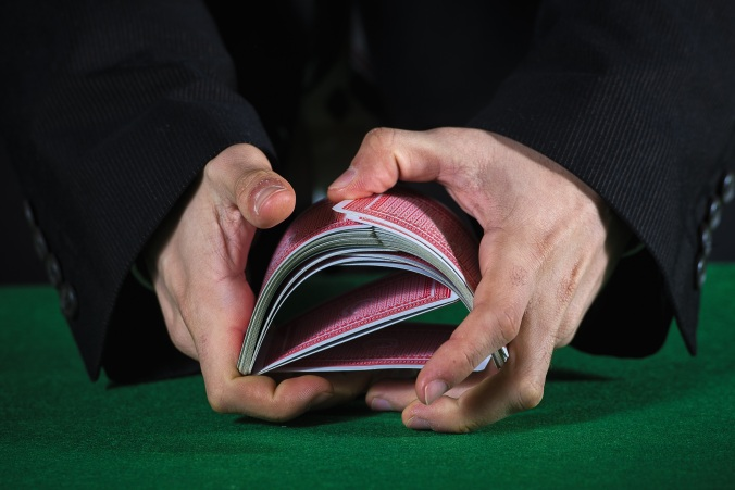 Closeup of hands shuffling cards casino